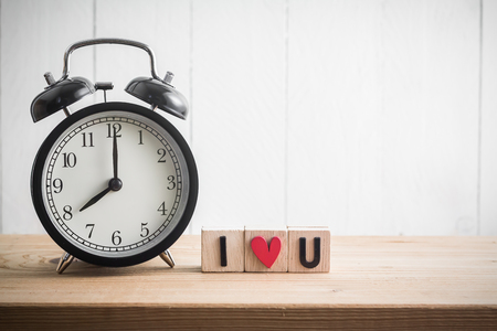 i love u: Vintage alarm clock with i love u in cube on wood table