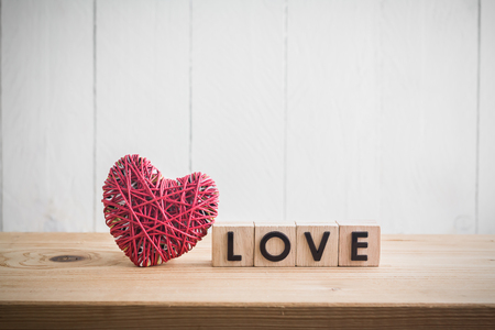 """Hilado del corazón rojo con el """"amor"""" en el cubo en la mesa de madera"""