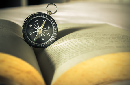 Compass on open old book Stock Photo