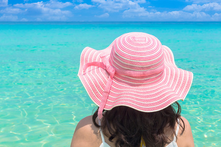 pink hat: Woman in big pink hat on the beach over sea background Stock Photo