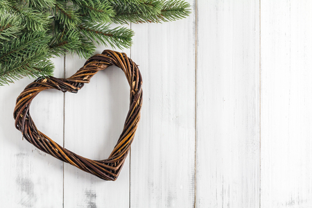 pine wreaths: Christmas fir tree branches with heart shaped wreaths  on white rustic wooden background with copy space for text Stock Photo