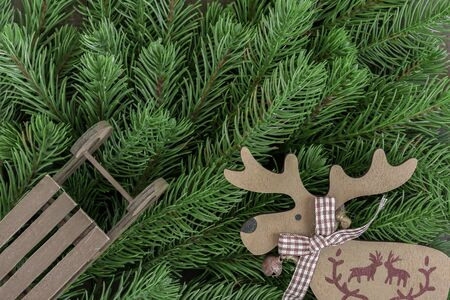 Wooden reindeers and sled ornament on fir tree branches background Stock Photo