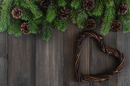 pine wreaths: Christmas fir tree branches with pine and heart shaped wreaths on dark rustic wooden background with copy space for text