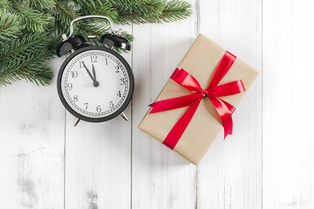 Christmas fir tree branches with gift box and alarm clock  on white rustic wooden background with copy space for text Stock Photo