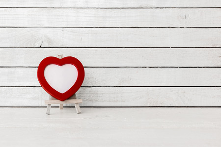 Red Heart Frame with wood art stand on white wood Background