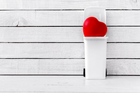 Red Heart Shaped in bins over white wood background Stock Photo