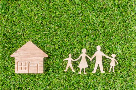 Wood Family Shaped and Home Shaped on green grass.  Green Family Concept. Stock Photo