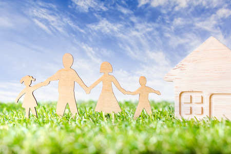 Wood Family Shaped with Wood Home Shaped  on green grass over beautiful sky.  Green Family Concept.