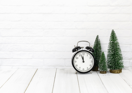 alarm clock and christmas tree on white wood table over white background with copy space Stock Photo