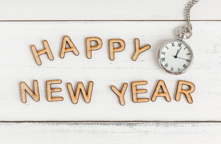 Happy New Year and clock from alphabet letters on wood table Stock Photo