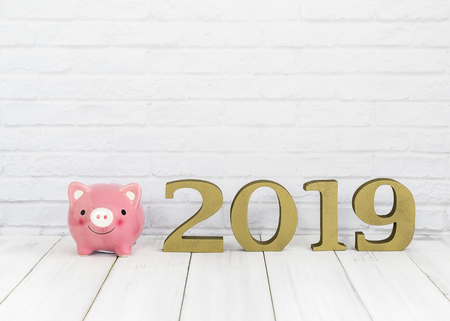 2019 new year and  piggy bank on white wood table over white background with copy space , saving concept