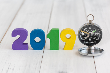 2019 new year and compass on white wood table