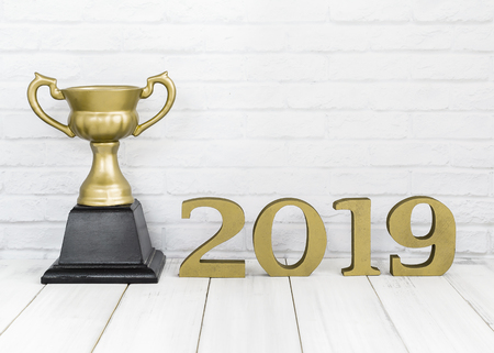 2019 new year and golden trophy on white wood table over white background with copy space , winner or success concept