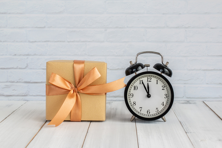 Gift box with alarm clock over wood table