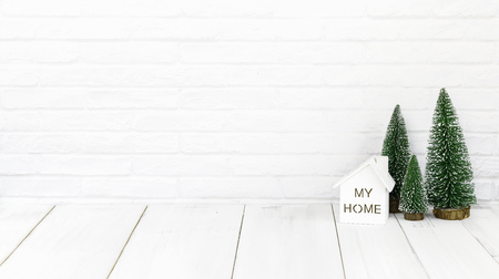 home and christmas tree on white wood table over white background with copy space