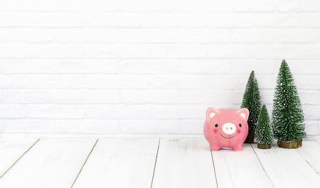 piggy bank and christmas tree on white wood table over white background with copy space , saving concept
