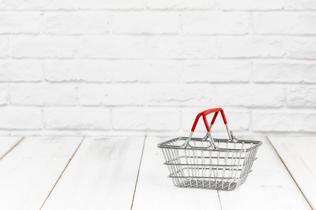 Basket on white wood background with copy space. shopping concept