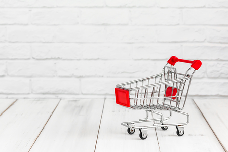 Trolley shopping cart on white wood background with copy space. shopping concept Stock fotó