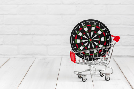 Dart board in trolley shopping cart on white wood background with copy space. find target concept. Stock fotó