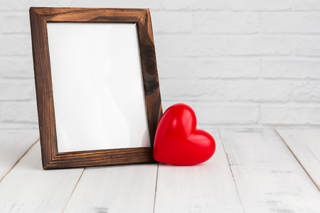 Photo frame and red heart on white wood table with copy sapce, love concept. Stock fotó - 122393064