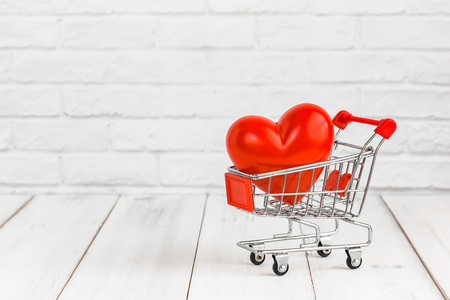 Red heart in trolley shopping cart on white wood background with copy space. love concept.
