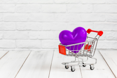 Violet heart in trolley shopping cart on white wood background with copy space. love concept.