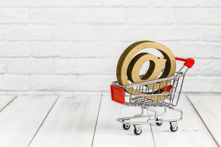 At sign in trolley shopping cart on white wood background with copy space. shopping online concept.