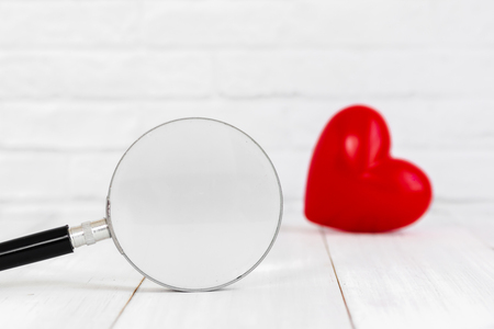 Magifying glass with red heart shaped on white background, find love concept