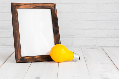 Photo frame and yellow light bulb on white wood table with copy sapce, idea concept.