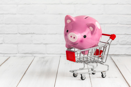 Piggy Bank in trolley shopping cart on white wood background with copy space. saving for shopping concept.