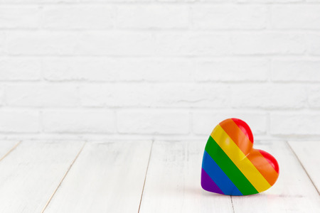 Rainbow heart shaped on white wood background with copy space
