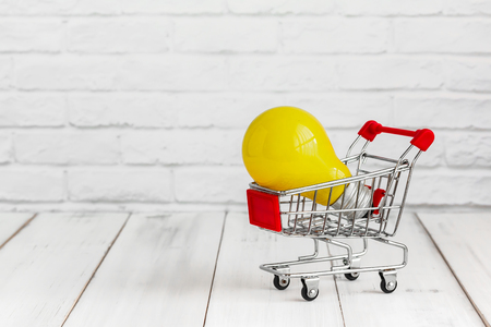 Yellow light bulb in trolley shopping cart on white wood background with copy space. buy idea concept.