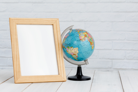 Photo frame and globe on white wood table with copy sapce, travel concept.