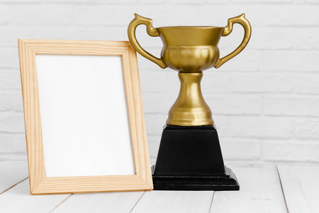 Photo frame and gold trophy on white wood table with copy sapce, winner concept.