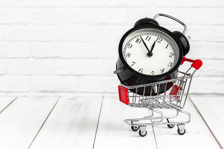 Alarm clock in trolley shopping cart on white wood background with copy space. time concept.
