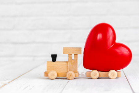 Red heart shaped on wood train over white background