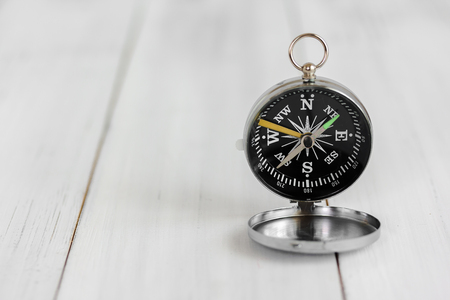 Compass on white wood table over white brick background with copy space.