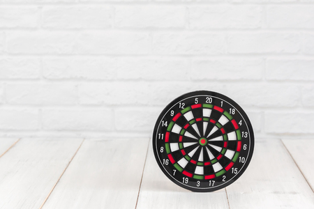 Dartboard on white wood table over white brick background with copy space. Stock fotó
