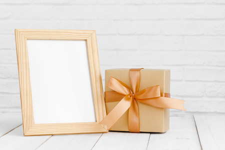 Photo frame and gift box on white wood table with copy sapce. Stock fotó