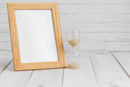 Photo frame and hourglass on white wood table with copy sapce, time concept.