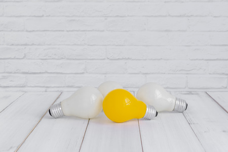Yellow and White light bulbs on white wood table over white brick background with copy space. Stock fotó