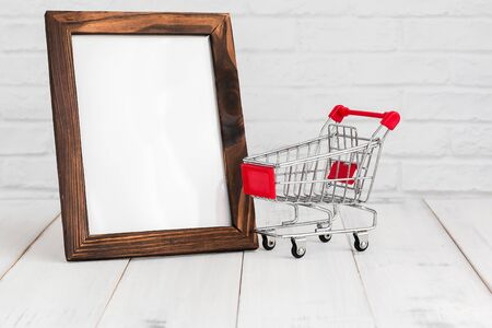 Photo frame and trolley shopping cart on white wood table with copy sapce, shopping concept. Zdjęcie Seryjne