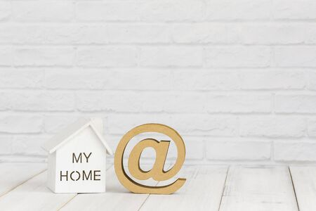 White home and at sign on white wood table over white brick background with copy space.