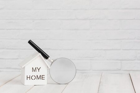 White home and magnifying on white wood table over white brick background with copy space. Zdjęcie Seryjne