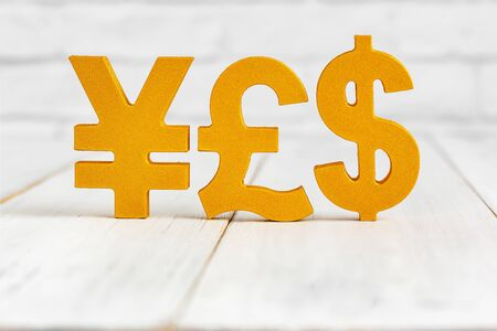 Dollar sign , Yen sign and pound sign on white wood table over white brick background with copy space.