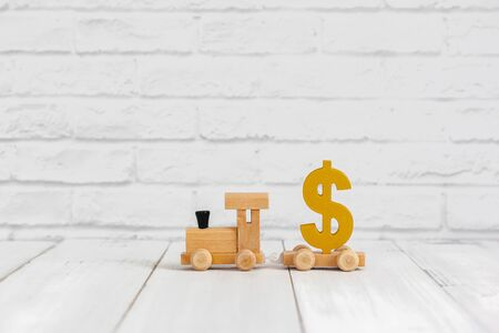 Golden dollar sign on wood train over white background with copy space