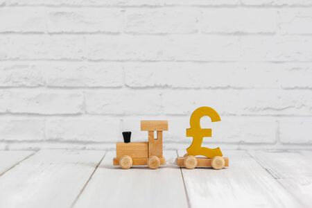Golden pound sign on wood train over white background with copy space