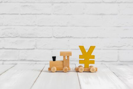 Golden yen sign on wood train over white background with copy space