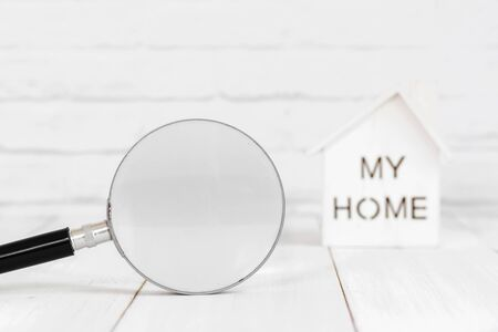Magnifying and home on white wood table over white brick background with copy space. Zdjęcie Seryjne