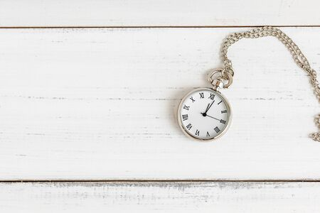 Necklace pocket watch on white wood table with copy space.